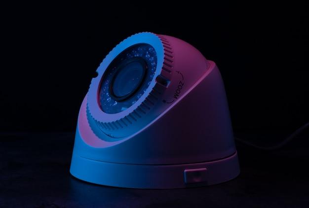 Ochrona aparatu na ciemnej ścianie w różowym i niebieskim świetle.