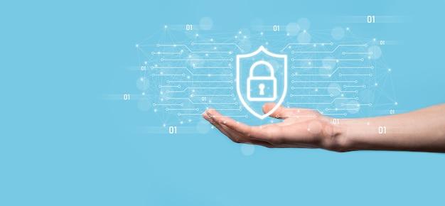 Ochrona komputera bezpieczeństwa sieci i bezpieczne pojęcie danych, biznesmen posiadający ikonę ochrony tarczy. symbol kłódki, pojęcie o bezpieczeństwie, cyberbezpieczeństwie i ochronie przed zagrożeniami.