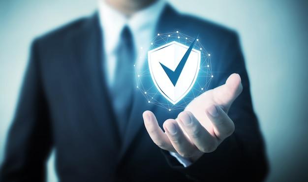 Ochrona komputera bezpieczeństwa sieci i bezpieczne swoje dane koncepcja, biznesmen posiadania tarczy chronić ikona