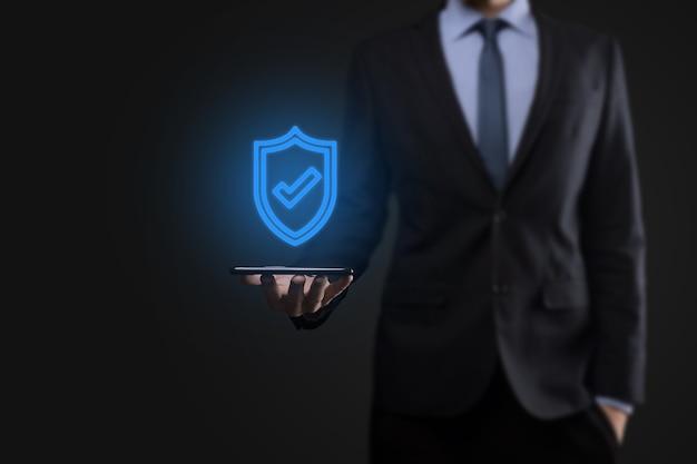 Ochrona komputera bezpieczeństwa sieci w rękach biznesmena. biznes, technologia, bezpieczeństwo cybernetyczne i koncepcja internetu - biznesmen naciskając przycisk tarczy na wirtualnych ekranach ochrona danych.