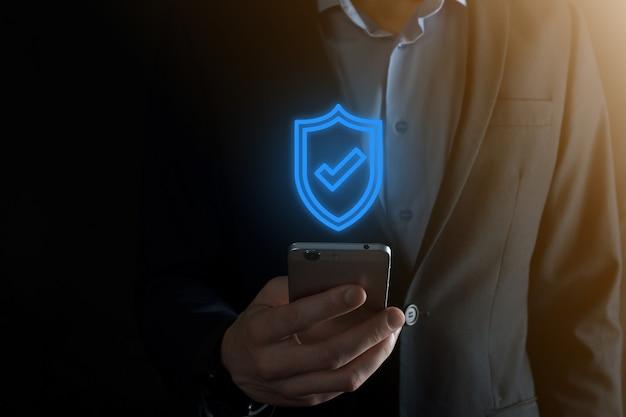Ochrona komputera bezpieczeństwa sieci w rękach biznesmena. koncepcja biznesowa, technologia, cyberbezpieczeństwo i internet - biznesmen naciskając przycisk tarczy na wirtualnych ekranach ochrona danych.