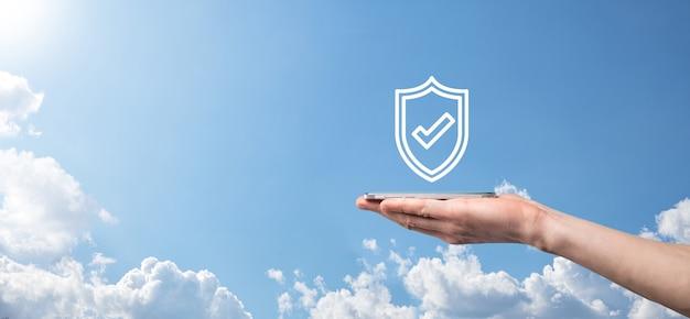 Ochrona komputera bezpieczeństwa sieci w rękach biznesmena. koncepcja biznesu, technologii, bezpieczeństwa cybernetycznego i internetu - biznesmen naciskający przycisk tarczy na wirtualnych ekranach ochrona danych