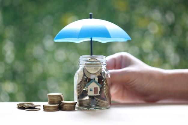 Ochrona, model domu i złote monety pieniądze w szklanej butelce ręką trzymającą parasol na naturalnym zielonym tle, ubezpieczenie finansów i koncepcja bezpiecznej inwestycji