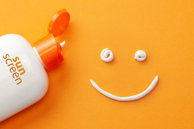 Ochrona przeciwsłoneczna na pomarańczowym tle. plastikowa butelka ochrony przeciwsłonecznej i białego kremu w kształcie uśmiechniętej buźki.