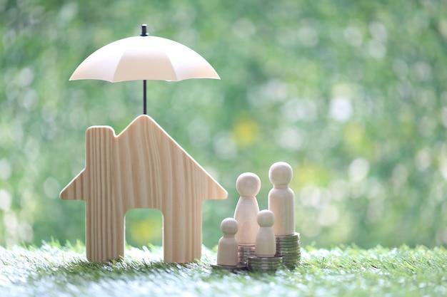 Ochrona, rodzina modeli na stosie monet pieniędzy z modelowym domem pod parasolem na naturalnym zielonym tle, ubezpieczenie finansowe i koncepcja bezpiecznej inwestycji