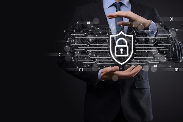 Ochrona sieci komputer bezpieczeństwa i bezpieczne pojęcie danych, biznesmen posiadający ikonę ochrony tarczy. symbol kłódki, pojęcie o bezpieczeństwie, cyberbezpieczeństwie i ochronie przed zagrożeniami.