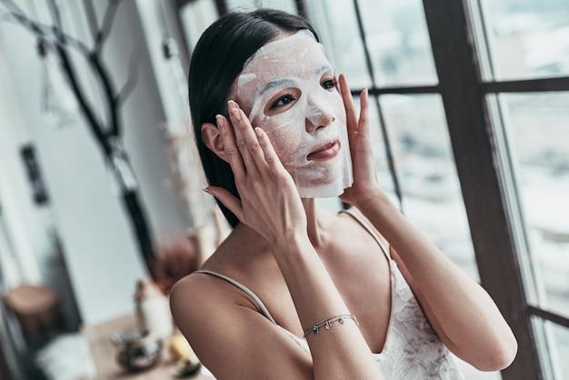 Ochrona skóry. atrakcyjna młoda kobieta nakłada maskę na twarz i odwraca wzrok, spędzając czas w domu