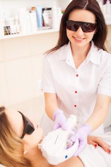 Ochrona skóry. dorosła kobieta o laserowe usuwanie włosów w profesjonalnym salonie kosmetycznym