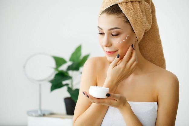 Ochrona skóry. kobieta o zdrowej twarzy stosowania kremu kosmetycznego pod oczami