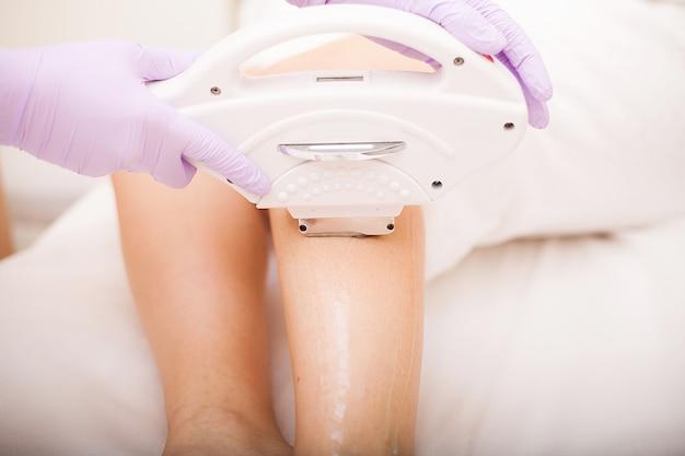 Ochrona skóry. kobieta w salonie kosmetycznym, depilacja laserowa nóg.