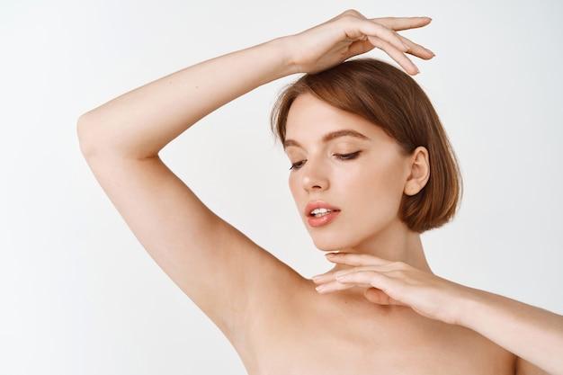 Ochrona skóry. kobieta z piękna twarz dotyka zdrowego portretu skóry twarzy. piękna uśmiechnięta modelka z naturalnym makijażem dotykająca świecącej nawilżonej skóry na białej ścianie