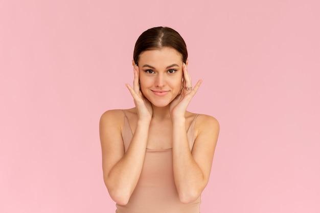 Ochrona skóry. kobieta z piękna twarz dotyka zdrowej skóry twarzy. uśmiechnięta modelka patrząc w kamerę i uśmiechając się na różowym tle.