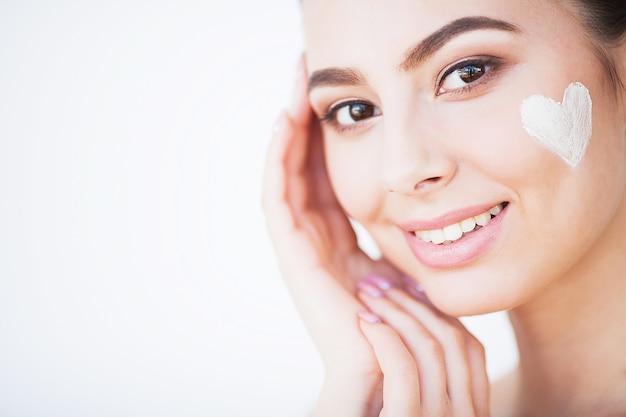 Ochrona skóry. kobieta z zdrową twarzą stosuje kosmetyczny krem pod oczy
