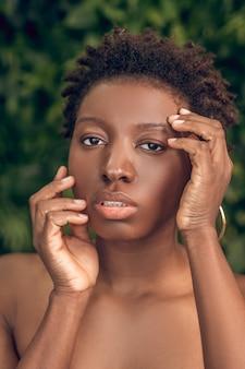 Ochrona skóry. młoda dorosła atrakcyjna afroamerykańska kobieta z nagimi ramionami dotykającymi twarzy na tle zielonych roślin