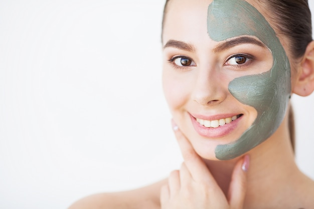 Ochrona skóry. młoda kobieta z kosmetyczną glinianą maską trzyma ogórek przy jej łazienką