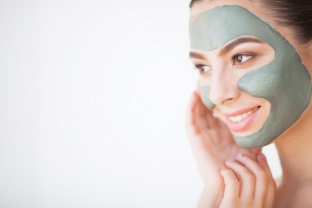 Ochrona skóry. młoda kobieta z kosmetyczną gliny maski mienia ogórkiem przy jej łazienką