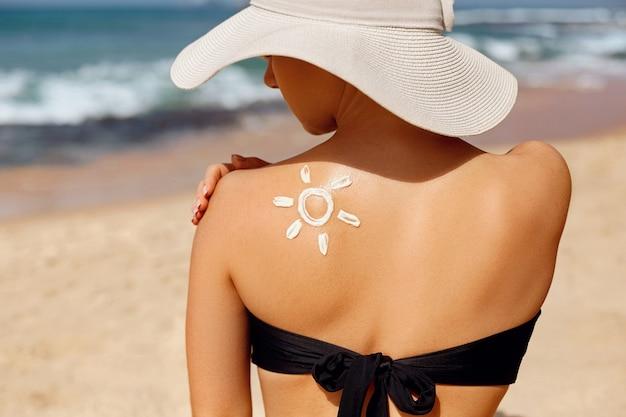 Ochrona skóry. ochrona przed słońcem. piękna kobieta stosuje krem do opalania na twarz.
