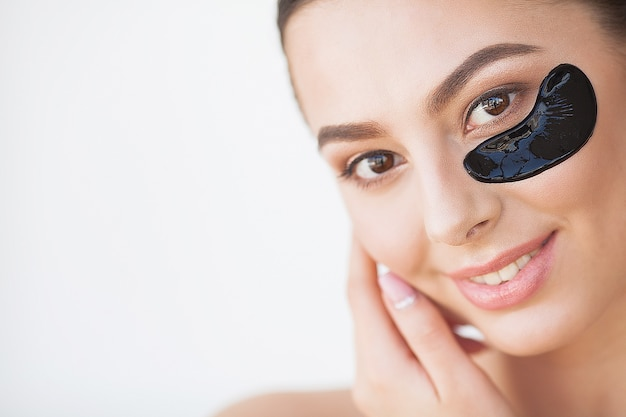 Ochrona skóry. piękna dziewczyna z kosmetycznymi czarnymi łatami pod oczami, doskonałą skórą i naturalnym makijażem.