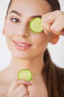 Ochrona skóry. piękna młoda kobieta z ogórkami na oczach