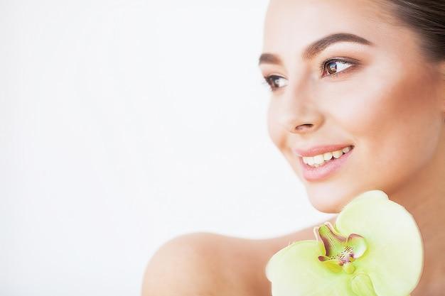Ochrona skóry. piękna modelka z doskonałej skóry i kwiat orchidei w pobliżu jej twarzy