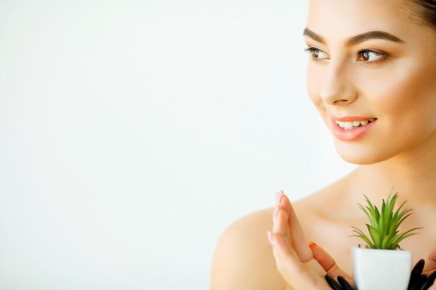 Ochrona skóry. piękna twarz młodej kobiety z kwiatem. zabieg upiększający. kosmetyka. salon kosmetyczny spa