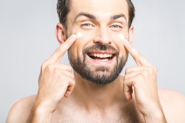 Ochrona skóry. przystojny młody bez koszuli mężczyzna stosuje śmietankę przy jego twarzą i patrzeje go podczas gdy stojący nad szarym tłem