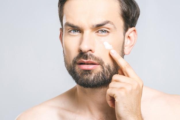 Ochrona skóry. przystojny młody bez koszuli mężczyzna stosuje śmietankę przy jego twarzą i patrzeje go z uśmiechem podczas gdy stojący nad szarym tłem