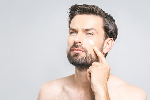 Ochrona skóry. przystojny młody bez koszuli mężczyzna stosuje śmietankę przy jego twarzą i przyglądającą up podczas gdy stojący nad szarym tłem