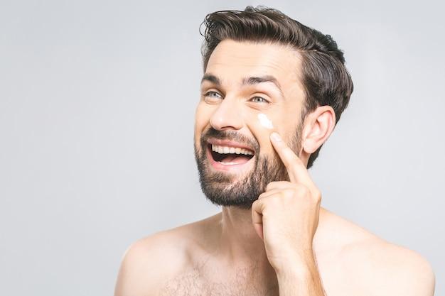 Ochrona skóry. przystojny szczęśliwy młody bez koszuli mężczyzna stosuje śmietankę przy jego twarzą i patrzeje go z uśmiechem podczas gdy stojący nad szarym tłem