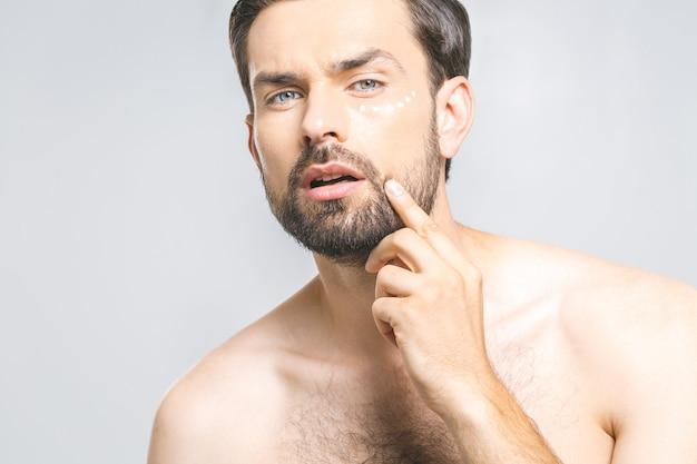 Ochrona skóry. przystojny szczęśliwy młody bez koszuli mężczyzna stosuje śmietankę przy jego twarzą i przyglądającą up podczas gdy stojący nad szarym tłem
