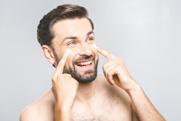 Ochrona skóry. przystojny szczęśliwy młody bez koszuli mężczyzna stosuje śmietankę przy jego twarzą i przyglądającą z uśmiechem up podczas gdy stojący nad szarym tłem