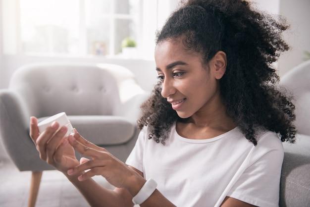 Ochrona skóry. radosna atrakcyjna kobieta trzyma butelkę kremu, jednocześnie dbając o swoją skórę