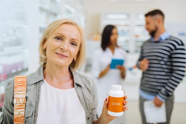 Ochrona skóry. zadowolona klientka wyrażająca pozytywne nastawienie podczas kupowania glicyny dla swojej skóry