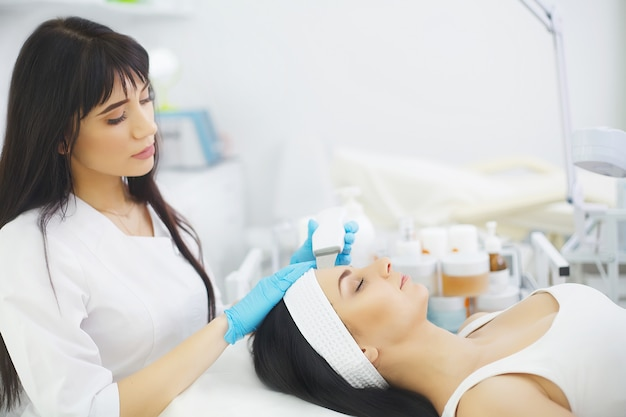 Ochrona skóry. zakończenie piękna kobieta otrzymywa ultradźwiękowego kawitacja peeling twarzy. procedura ultradźwiękowego oczyszczania skóry. zabieg upiększający. kosmetyka. beauty spa salon.