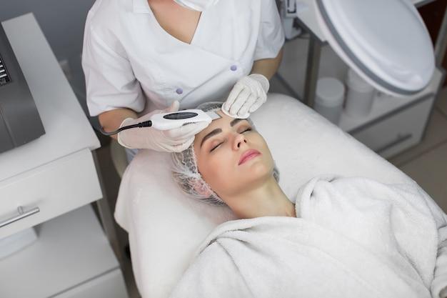 Ochrona skóry. zbliżenie: piękna kobieta odbiera peeling twarzy kawitacji ultradźwiękowej. procedura ultradźwiękowego oczyszczania skóry. zabieg upiększający. kosmetyka. salon kosmetyczny spa.