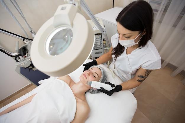 Ochrona skóry. zbliżenie: piękna kobieta odbiera peeling twarzy kawitacji ultradźwiękowej.