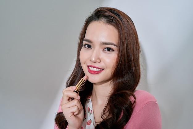 Ochrona ust. piękna kobieta z piękna twarz, seksowne pełne usta stosując balsam do ust, szminka trzymać. portret modelki z naturalnym makijażem. koncepcja kosmetyki do pielęgnacji skóry ust. wysoka rozdzielczość