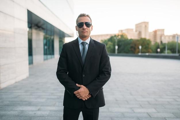 Ochroniarz męski w garniturze, na zewnątrz ochronna słuchawka i okulary przeciwsłoneczne.