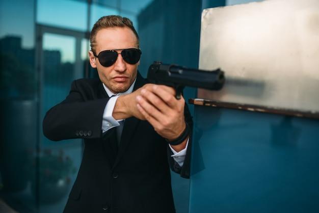 Ochroniarz w garniturze i okularach przeciwsłonecznych z pistoletem w ręce