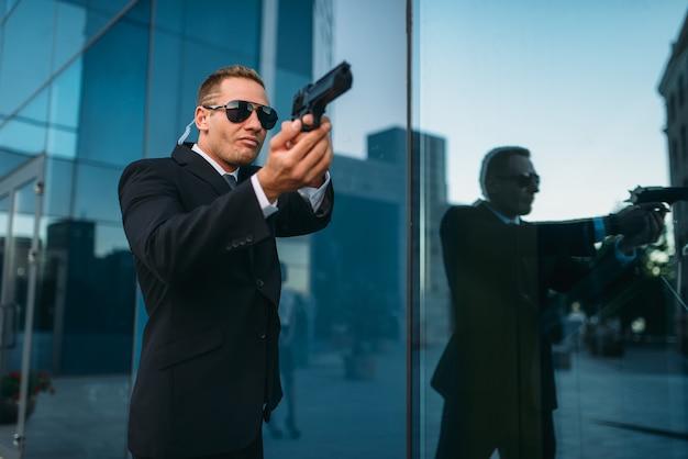 Ochroniarz z zabezpieczającą słuchawką i pistoletem w rękach