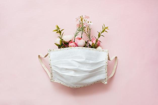 Ochronna maska chirurgiczna z ułożonymi kwiatami na różowym tle