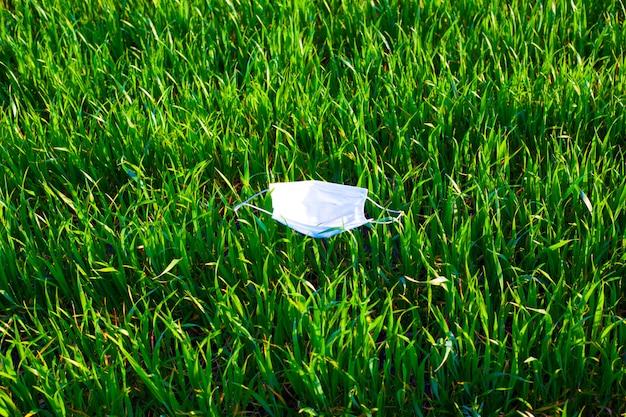 Ochronna maska medyczna na trawie, letnia epidemia koronawirusa covid-19.
