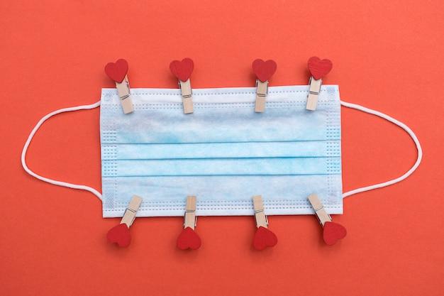 Ochronna maska medyczna z spinaczami do bielizny z sercem. pojęcie miłości w nowej normalnej rzeczywistości.