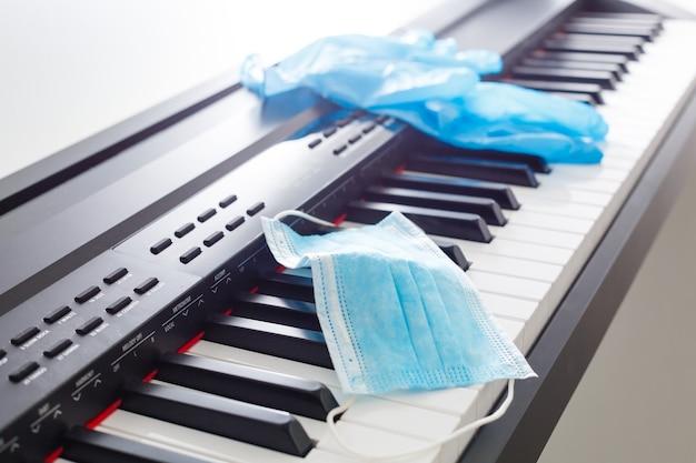 Ochronna medyczna maska przeciw grypie na zbliżeniu klawiatury fortepianu