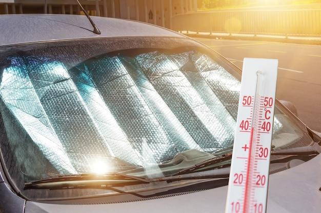 Ochronna powierzchnia odbijająca pod przednią szybą samochodu osobowego zaparkowanego w upalny dzień, nagrzana promieniami słonecznymi. termometr pokazuje temperaturę wewnątrz auta.