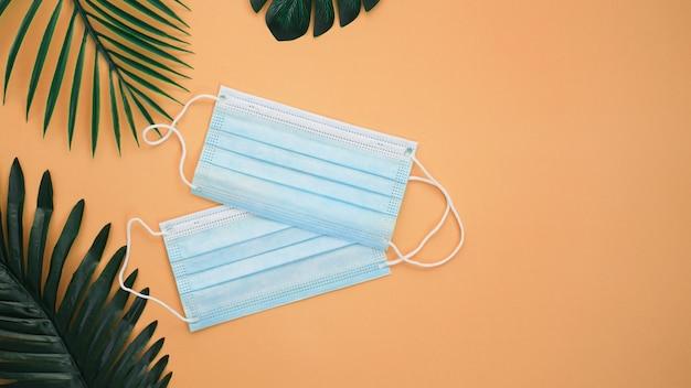 Ochronne maski medyczne na tle z liści palmowych. koncepcja wakacji podczas wirusa.