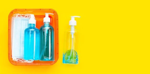 Ochronne maski medyczne z płynnym środkiem odkażającym alkohol i sprayem na żółtym tle.