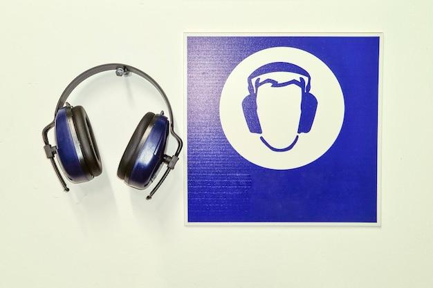 Ochronne niebieskie słuchawki przemysłowe i symbol informacyjny na ścianie