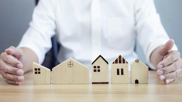 Ochronny gest mężczyzny i modelu domu koncepcja bezpieczeństwa w domu