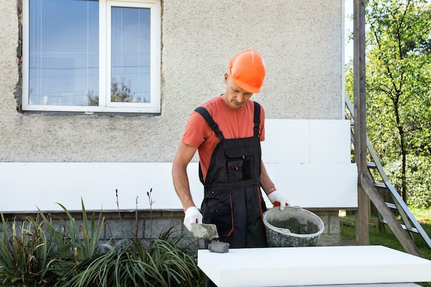 Ocieplenie domu pianką. pracownik nakłada klej na płytę styropianową.